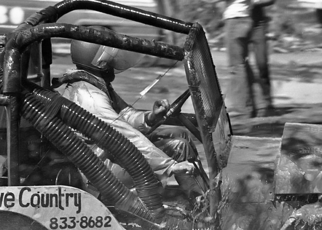 Racer driving modified racing willys jeep through the mud in Yakima