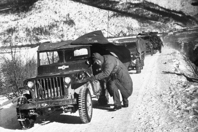 "David Douglas Duncan / TIME & LIFE Pictures.U.S. Marine crouching down next to his jeep while leading a convoy of vehicles during the 1st Marine Division's retreat down canyon road they called ""Nightmare Alley,"" after being cut off by the Red Chinese and under fire from nearby hills in December 1950."