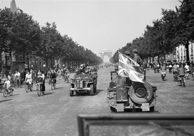 An_AFPU_(Army_Film_and_Photographic_Unit)_jeep_displaying_a_large_union_flag_drives_down_the_Champs_Elysees_in_Paris,_26_August_1944._BU89