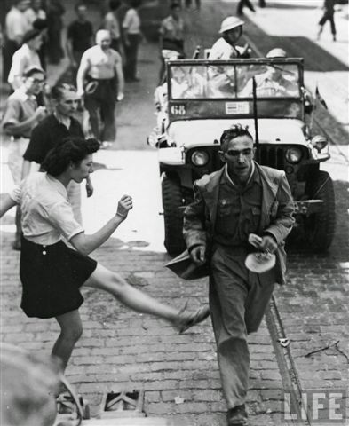 French woman vents her anger towards a German POW with a kick, 1944