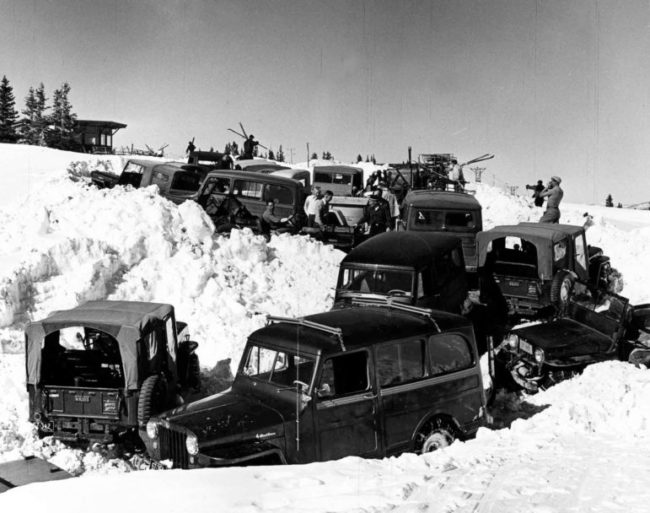 One b/w photograph and negative of about 10-15 jeeps and cars parked up near the top of Aspen Mountain. The Sundeck and lift towers can be seen in the background. There are skiers near the cars getting their equipment out of the cars. Sitting in the jeep is Dave Stapleton, John Thorpe is standing next to him (white shirt, buzz cut), Neil Beck is standing in front of John (grey shirt), and Euclid Worden in black cap. 1954-.