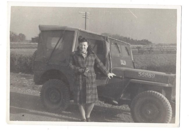 1945-lady-standing-next-to-jeep